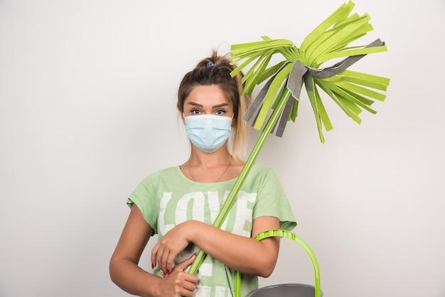 Giovane casalinga con maschera facciale che tiene mop sul muro bianco.