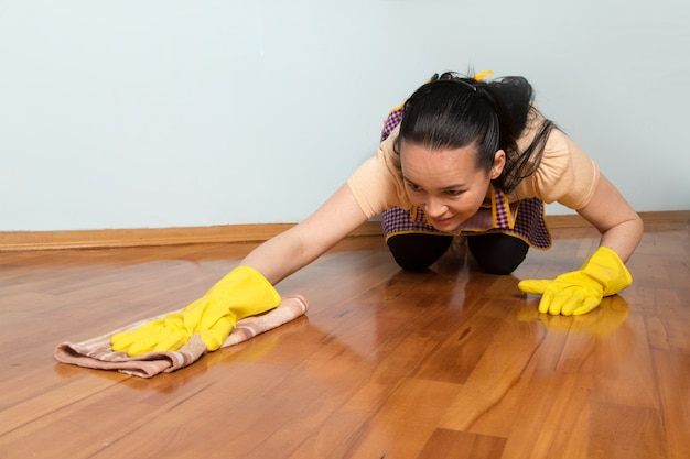 Young housewife with yellow gloves cleaning the floor