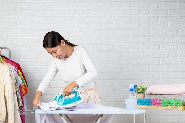 Молодые домохозяйки, использующие утюги, гладят свою одежду на белом кирпиче.