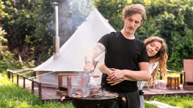 Young hugging couple frying meat on the grill. greenery around. glamping