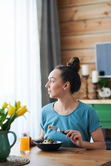 テーブルに座って、ベジタリアンパスタとオレンジジュースを持ちながらキッチンの窓から見ている空腹の若い女性
