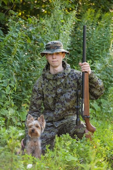 Young hunter with a gun and yorkshire terrier hunting in the forest.
