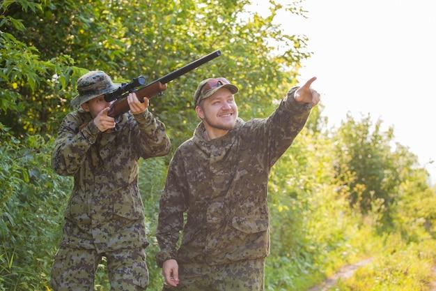 Молодые охотники с ружьем на охоте в лесу. пародия на охотников