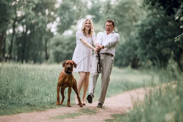 若い夫と彼の妻が公園を散歩しているペットの犬と一緒に。健康的なライフスタイルの概念