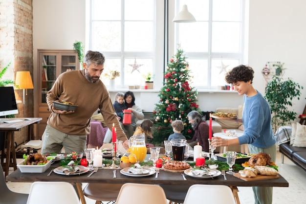 Молодые муж и жена склоняются над накрытым праздничным столом, кладут стаканы и жареные овощи перед семейным рождественским ужином