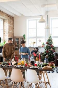 Молодые муж и жена стоят у сервированного праздничного стола, накрывая домашнюю еду, напитки и десерты перед семейным рождественским ужином