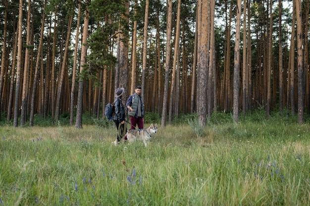 허스키 강아지와 함께 산책하는 젊은 남편과 아내