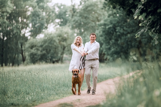 Young husband and his wife have fun with their pet dog