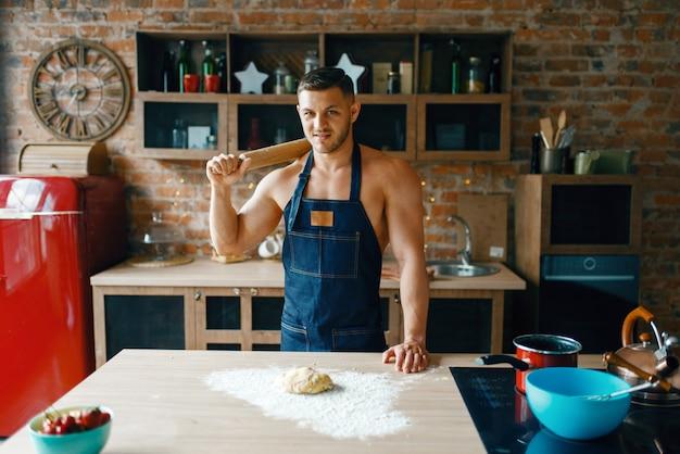 부엌에서 요리하는 속옷에 젊은 남편. 집에서 아침 식사를 준비하는 앞치마에 벌거 벗은 남자, 옷없이 음식 준비