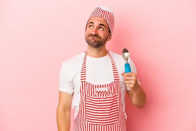 目標と目的を達成することを夢見てピンクの背景に分離されたスプーンを保持している若いアイスクリームメーカーの男 Premium写真