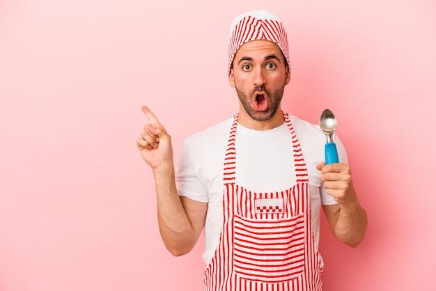 側面を指しているピンクの背景に分離されたスプーンを保持している若いアイスクリームメーカーの男