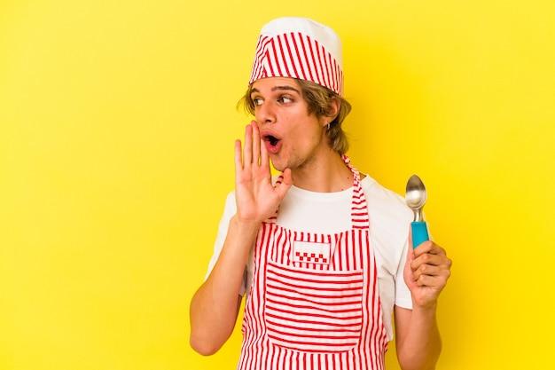 黄色の背景に分離されたスプーンを保持している化粧をしている若いアイスクリームメーカーの男は、秘密の熱いブレーキングニュースを言って脇を見ています