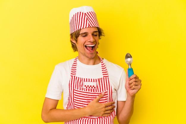 笑って楽しんで黄色の背景に分離されたスプーンを保持している化粧の若いアイスクリームメーカーの男。