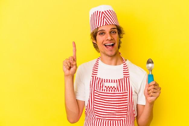 指でナンバーワンを示す黄色の背景に分離されたスプーンを保持している化粧の若いアイスクリームメーカーの男。