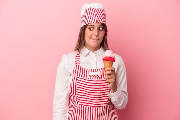 ピンクの背景に分離されたアイスクリームを保持している若いアイスクリームメーカーの女性は混乱し、疑わしく、不安を感じています。