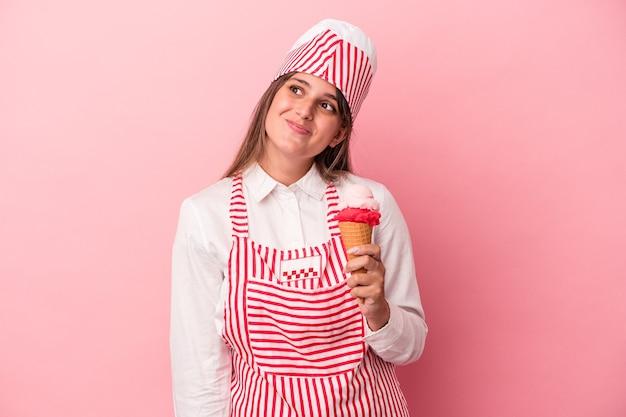 目標と目的を達成することを夢見てピンクの背景に分離されたアイスクリームを保持している若いアイスクリームメーカーの女性