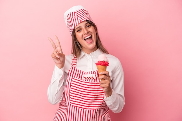 ピンクの背景に分離されたアイスクリームを持っている若いアイスクリームメーカーの女性は、指で平和のシンボルを喜んで気楽に示しています。