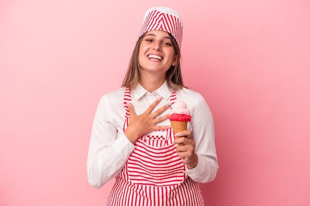 ピンクの背景に分離されたアイスクリームを保持している若いアイスクリームメーカーの女性は、胸に手を置いて大声で笑います。