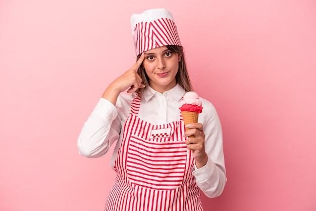 ピンクの背景に分離されたアイスクリームを保持している若いアイスクリームメーカーの女性は、指で寺院を指して、考えて、タスクに焦点を当てています。