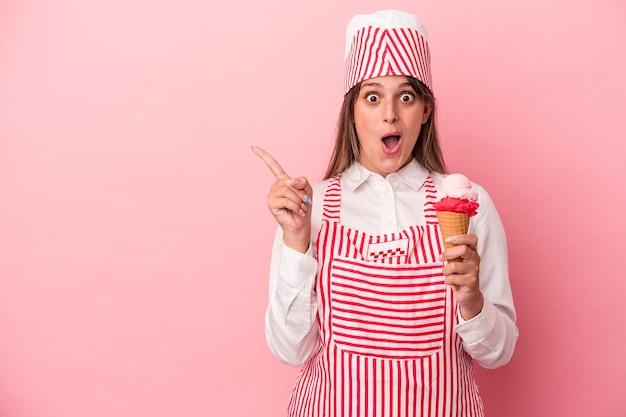 側面を指しているピンクの背景に分離されたアイスクリームを保持している若いアイスクリームメーカーの女性