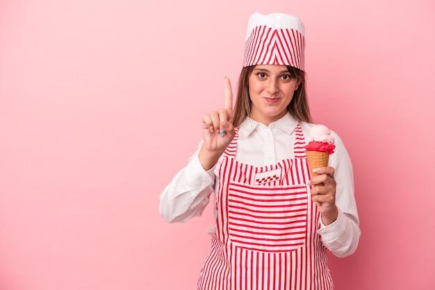 指でナンバーワンを示すピンクの背景に分離されたアイスクリームを保持している若いアイスクリームメーカーの女性。