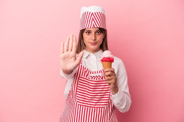 ピンクの背景に分離されたアイスクリームを保持している若いアイスクリームメーカーの女性は、一時停止の標識を示している手を伸ばして立って、あなたを防ぎます。