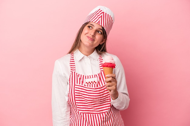 Young ice cream maker woman holding ice cream isolated on pink background dreaming of achieving goals and purposes