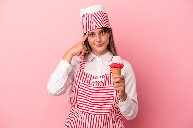 Young ice cream maker woman holding ice cream isolated on pink background pointing temple with finger, thinking, focused on a task.