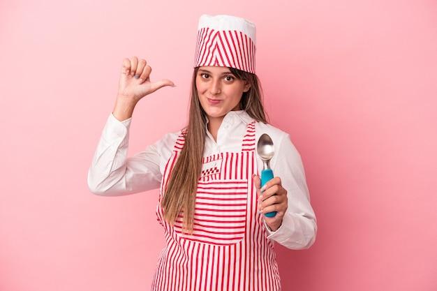 ピンクの背景に分離されたスプーンを保持している若いアイスクリームメーカーの女性は、誇りと自信を持って、従うべき例を感じます。