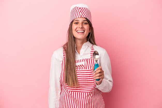 ピンクの背景に分離されたスプーンを保持している若いアイスクリームメーカーの女性は幸せ、笑顔、陽気な。