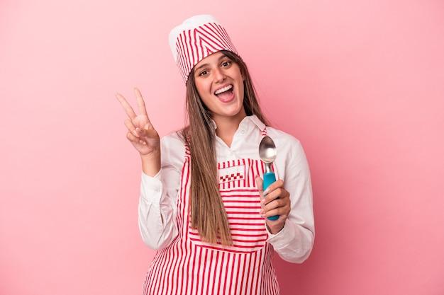 ピンクの背景に分離されたスプーンを持っている若いアイスクリームメーカーの女性は、指で平和のシンボルを喜んで気楽に示しています。