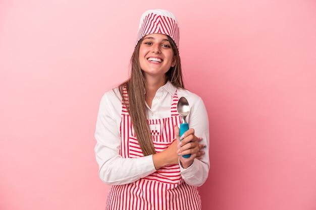 笑って楽しんでピンクの背景に分離されたスプーンを保持している若いアイスクリームメーカーの女性。