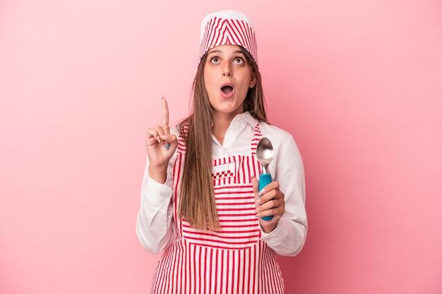 開いた口で逆さまを指しているピンクの背景に分離されたスプーンを保持している若いアイスクリームメーカーの女性。
