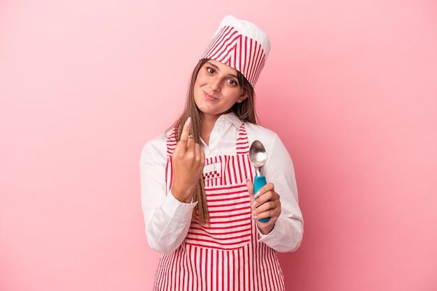 ピンクの背景に分離されたスプーンを持っている若いアイスクリームメーカーの女性は、招待が近づくようにあなたに指を指しています。