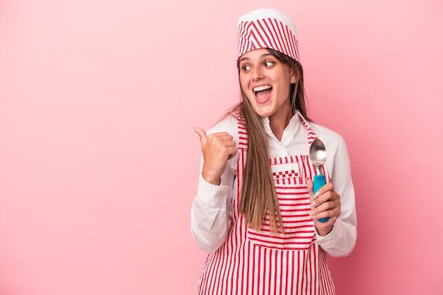 ピンクの背景に分離されたスプーンを持っている若いアイスクリームメーカーの女性は、親指の指を離れて、笑って気楽にポイントします。