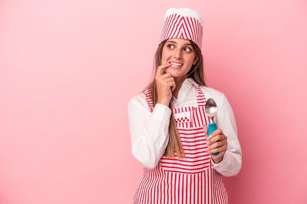 ピンクの背景に分離されたスプーンを保持している若いアイスクリームメーカーの女性は、コピースペースを見ている何かについて考えてリラックスしました。