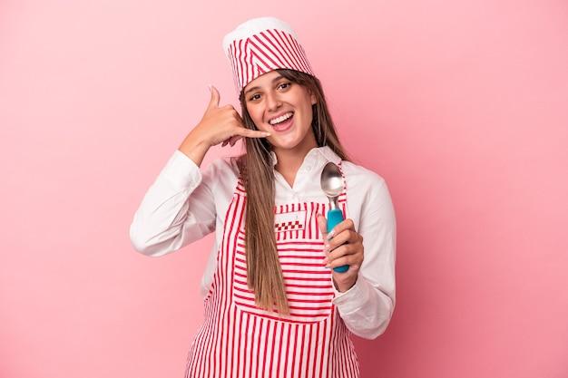 指で携帯電話の呼び出しジェスチャーを示すピンクの背景に分離されたスプーンを保持している若いアイスクリームメーカーの女性。