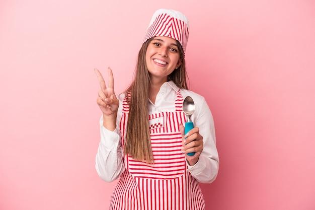 指で2番目を示すピンクの背景に分離されたスプーンを保持している若いアイスクリームメーカーの女性。