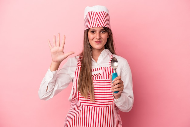ピンクの背景に分離されたスプーンを持っている若いアイスクリームメーカーの女性は、指で5番目を示す陽気な笑顔を浮かべています。
