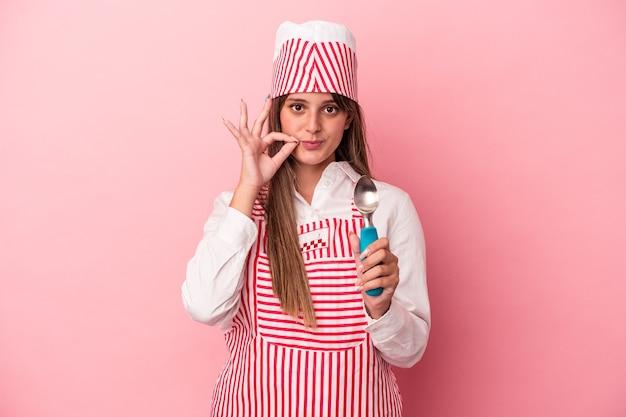 秘密を保持している唇に指でピンクの背景に分離されたスプーンを保持している若いアイスクリームメーカーの女性。
