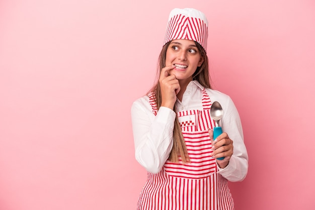 Young ice cream maker woman holding spoon isolated on pink background relaxed thinking about something looking at a copy space.