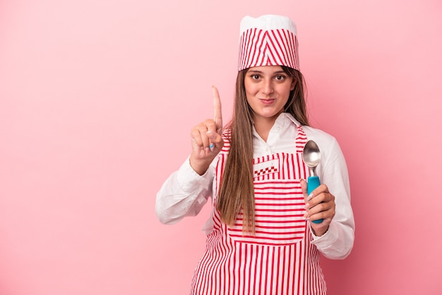 Young ice cream maker woman holding spoon isolated on pink background showing number one with finger.