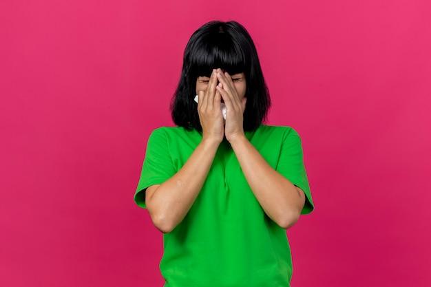 コピースペースで深紅色の背景に分離された顔くしゃみに手を保持ナプキンを保持している若い病気の白人の女の子
