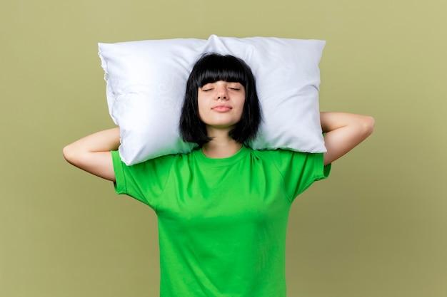 Молодая больная кавказская девушка держит подушку под головой с закрытыми глазами на оливково-зеленом фоне