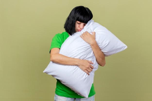 コピースペースのあるオリーブグリーンの壁に隔離された目を閉じてキスジェスチャーをしている枕を抱き締める若い病気の白人の女の子