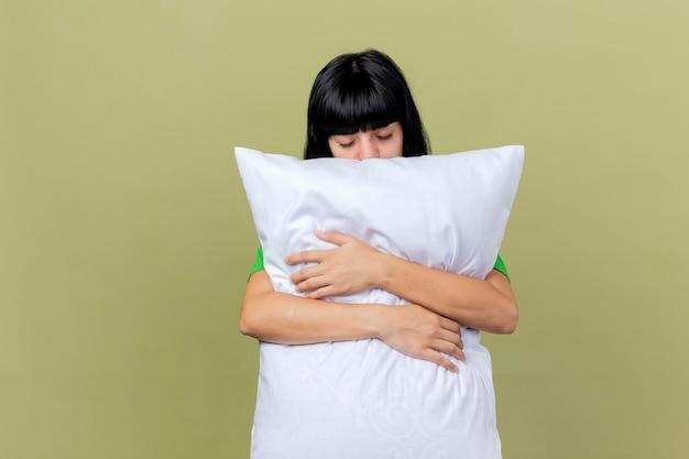 コピースペースとオリーブグリーンの背景に分離された目を閉じて枕を抱き締める若い病気の白人の女の子