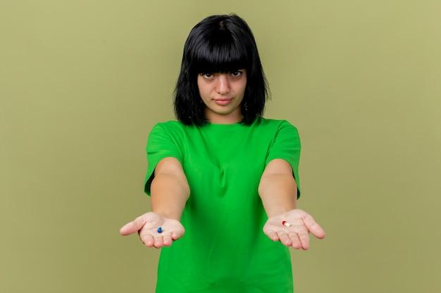 Giovane ragazza caucasica malata che allunga le capsule mediche verso la macchina fotografica che guarda l'obbiettivo isolato su fondo verde oliva con lo spazio della copia