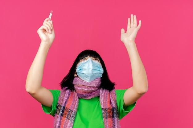 Giovane ragazza caucasica malata che indossa la maschera e la sciarpa che tiene termometro che osserva in su e che alza le mani in su pregando e benedicendo dio isolato su fondo cremisi con lo spazio della copia