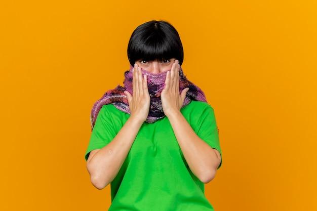복사 공간 오렌지 벽에 고립 된 스카프에 손을 유지 스카프로 입을 덮고 스카프를 착용하는 젊은 아픈 백인 여자