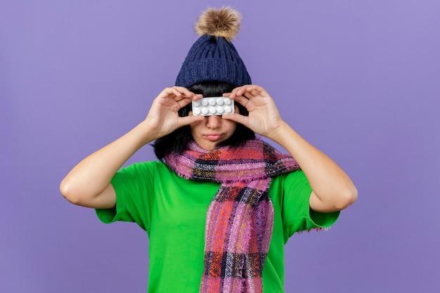 冬の帽子と紫色の背景で隔離の目の前にタブレットのパックを保持しているスカーフを身に着けている若い病気の白人の女の子